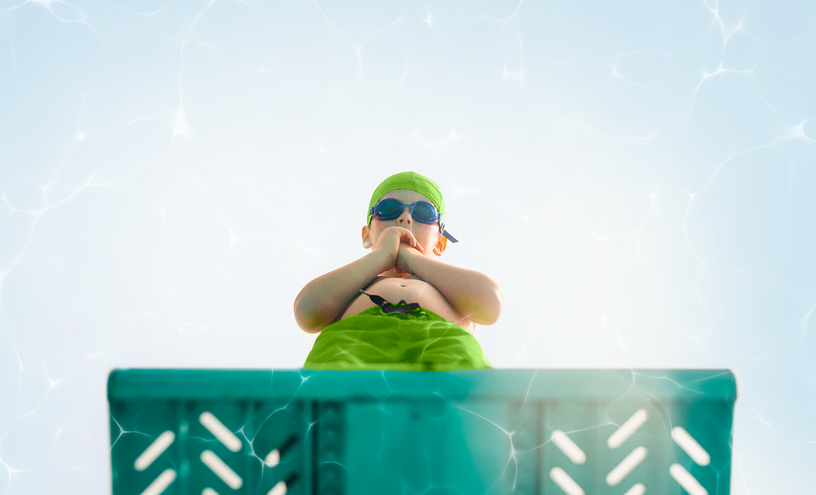 Underwater view of boy anxiously standing at the edge of a diving board while looking down at the water.